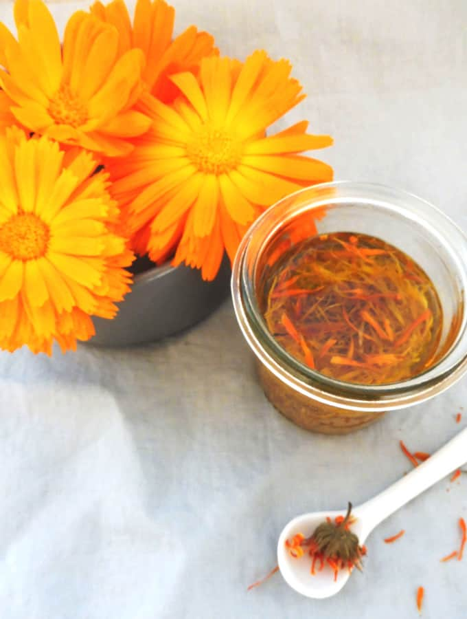 Calendula oil with marigold and white spoon