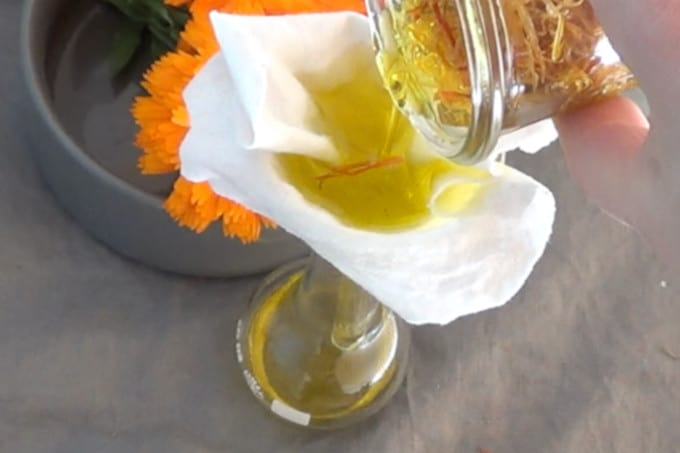 pouring calendula petals over a sieve