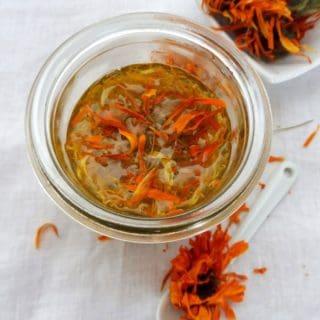 herbal oil in glass jar with dry calendula flower
