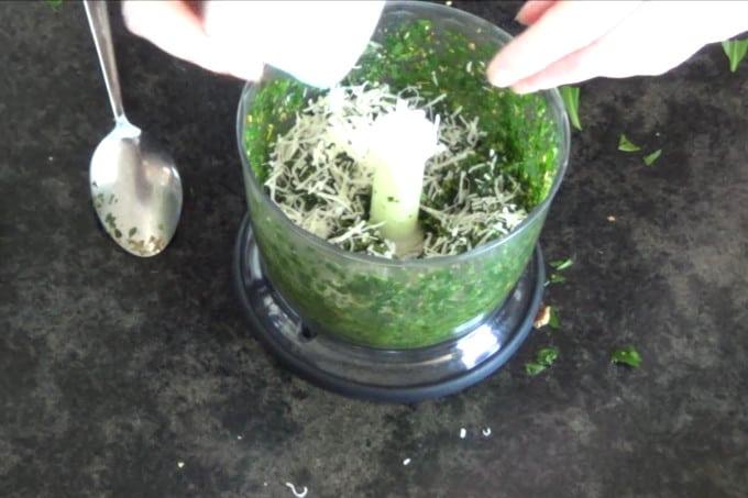 adding parmezan cheese into pesto in food processor