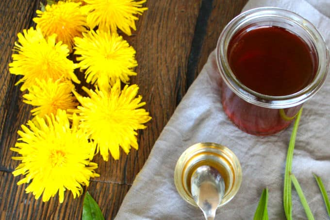 syrup with dandelion blossoms and spoon