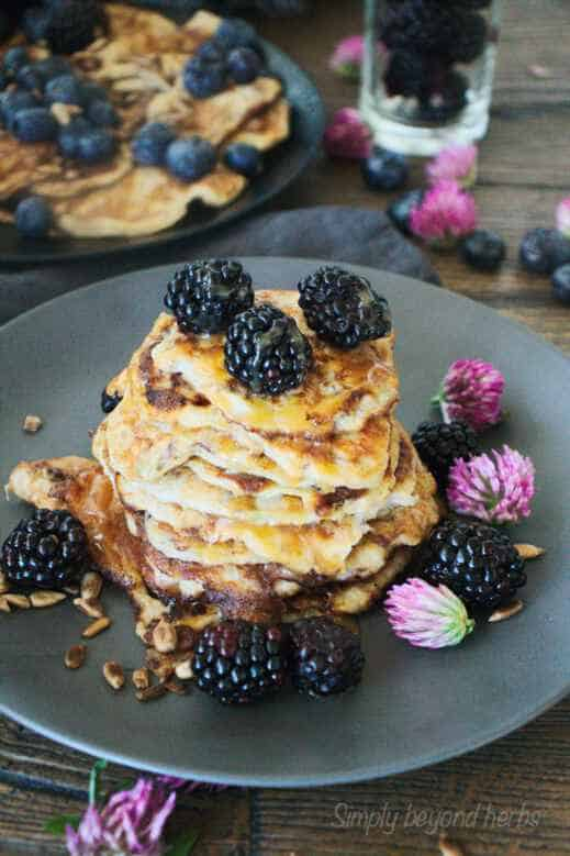two plates of banana pancakes with red clover and blackberries