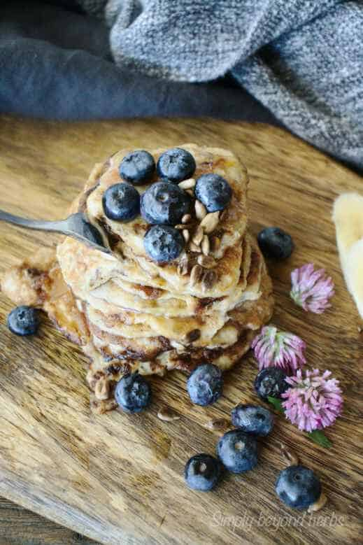 healthy pancakes with banana and red clover decorated with blueberries