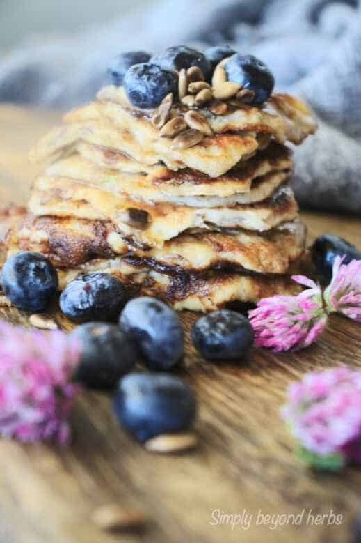 pile of banana pancakes decorated with red clover and blueberries