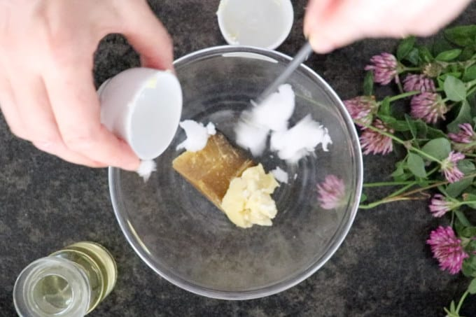 Process of making homemade lip balm. Adding coconut oil to the mixture