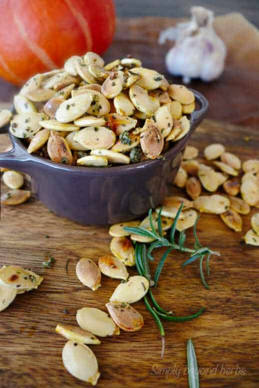 bowl of pumpkin seeds with pumkin and garlic in the background