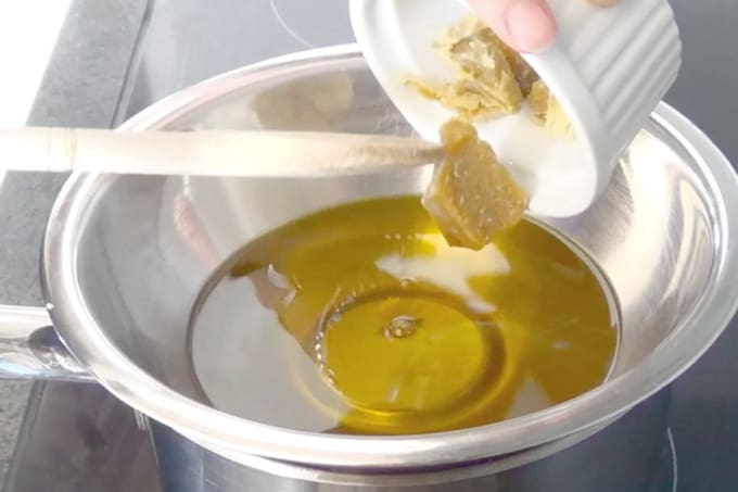 process of making dandelion salve - adding beeswax to the mixture