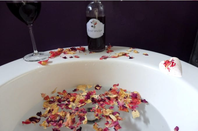 romantic bath with rose petals, bath bombs, rose water and glass of wine.